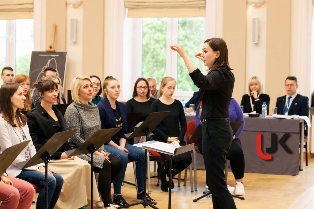 Kobieta dyryguje, w tle widać pozostałych uczestników